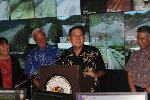 """HDOT Director Ford Fuchigami (at the podium), along with State Senator Michelle Kidani (left), Honolulu Mayor Kirk Caldwell and Governor David Ige, announce the annual """"Beat the School Jam"""" campaign to encourage the public to plan ahead and inform motorists of the latest traffic relief improvements projects."""