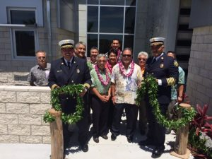State executives and head airport fire officers celebrate the completion of the new ARFF station at Hilo International Airport by untying the maile lei. From left to right: Steven Santiago, Assistant Airport District Manager; Chief Nawai Chartrand, Airport Fire Commander; Mayor Billy Kenoi; Ross Higashi, Airports Division Deputy Director; Representative Clift Tsuji; Representative Mark Nakashima; Senator Kaialii Kahele; Wil Okabe, Governer Ige's East Hawaii Representative; Representative Richard Onishi; Chief Martinez Jacobs, Airports Fire Chief.