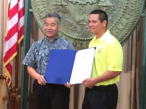 Governor David Ige signs a proclamation announcing August as Pedestrian Safety Month with Ed Sniffen, Highways Division Deputy Director.